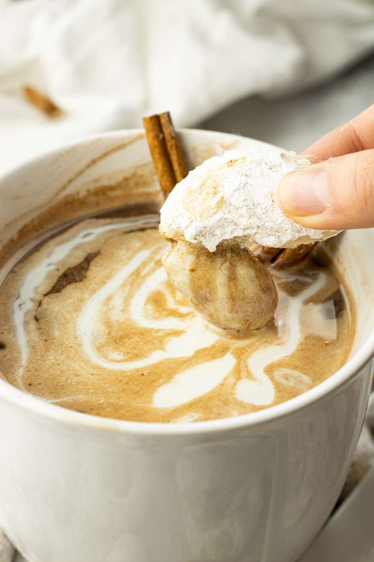 dipping powdered sugar coated cookies into hot chocolate
