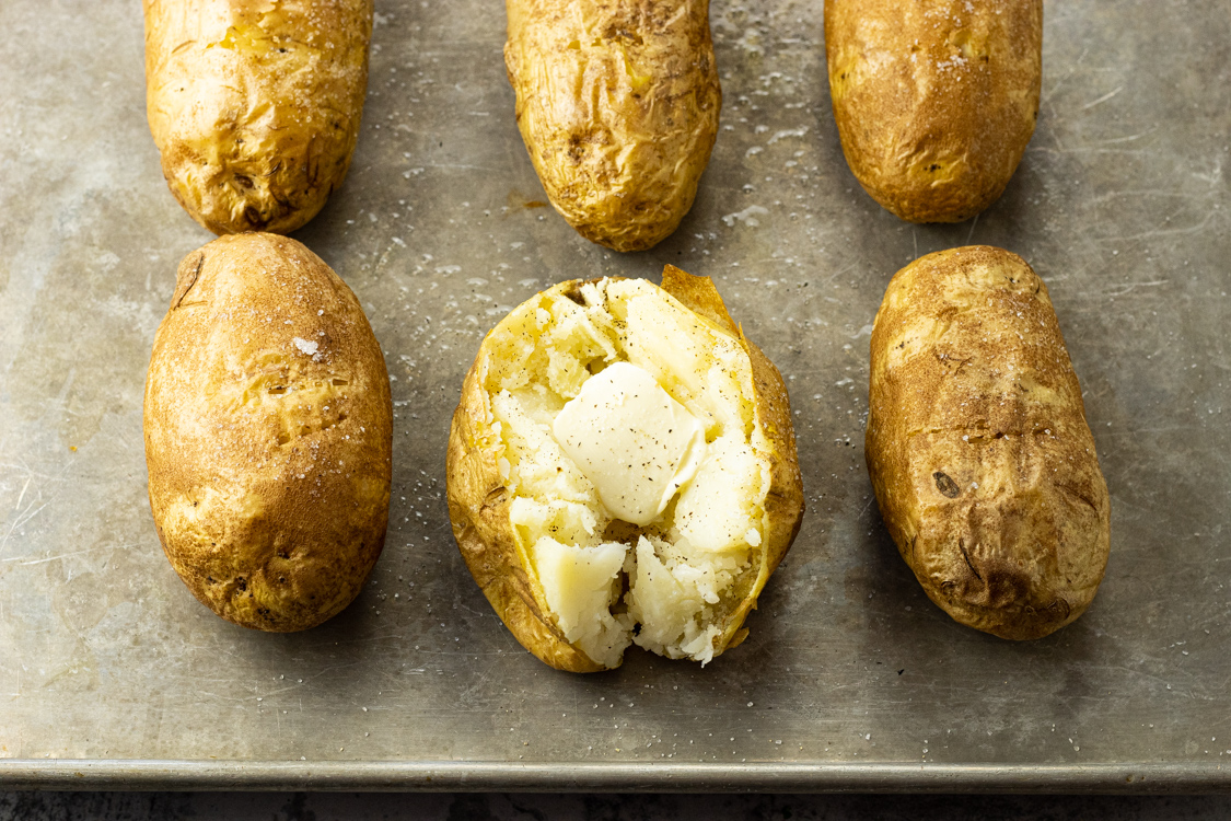 baked russet potatoes on a baking sheet with one split open with butter