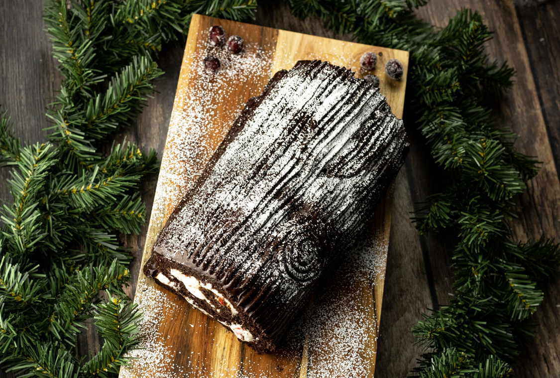chocolate yule log cake on a wooden platter