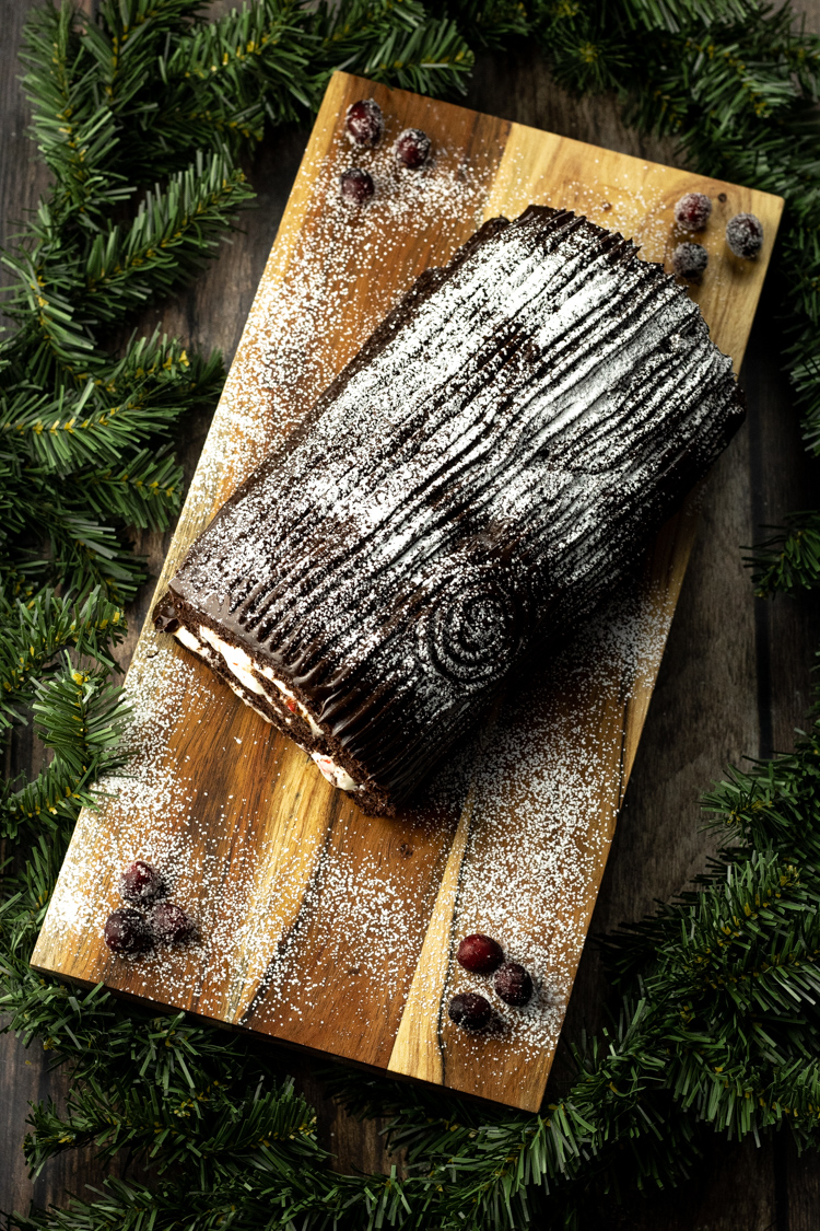 chocolate yule log cake on a wooden platter surrounded by evergreen pines