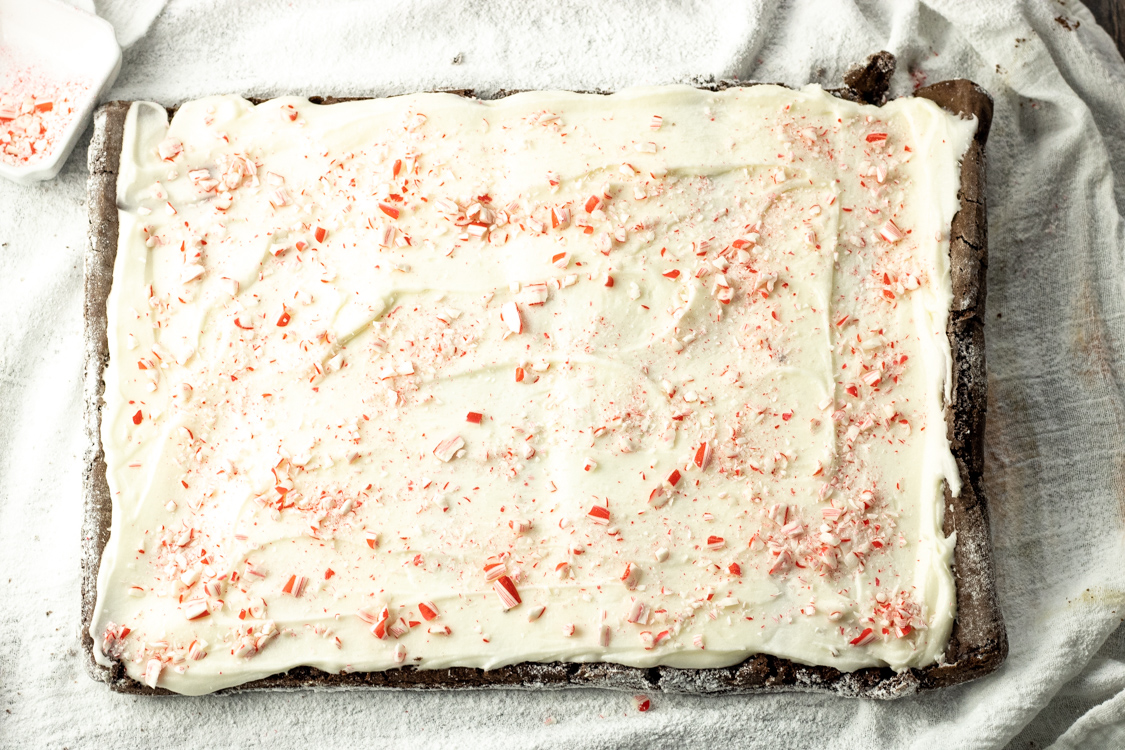 frosting rolled cake with white frosting topped with crushed candy canes