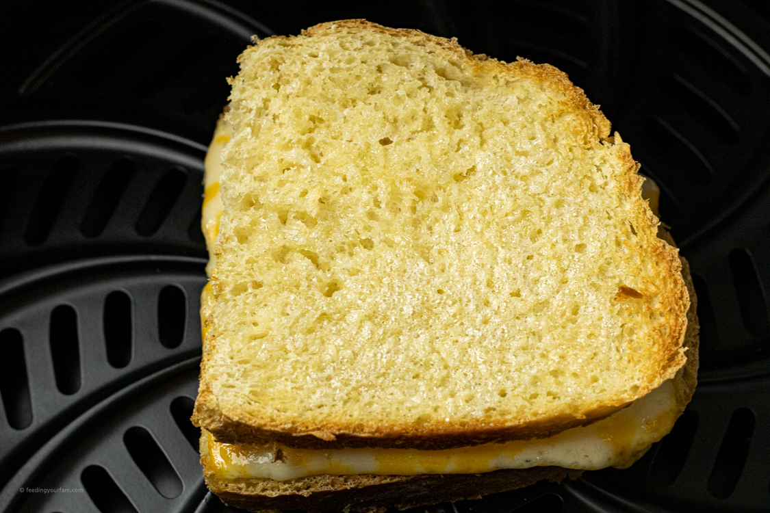 flipped cheese sandwich with cheese in an air fryer basket