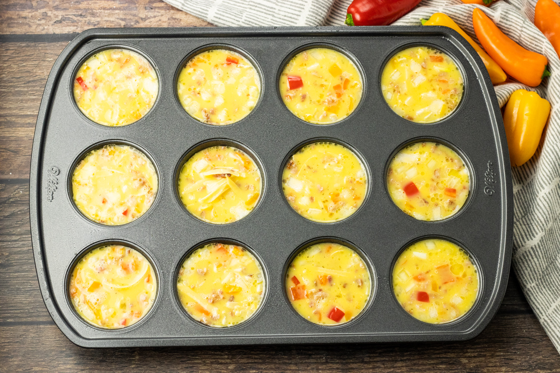 muffin tin pan full of scrambled bacon egg mixture