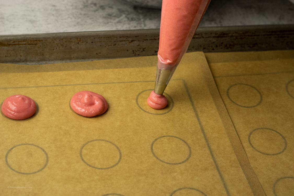 piping pink cookies onto parchment paper lined baking sheet