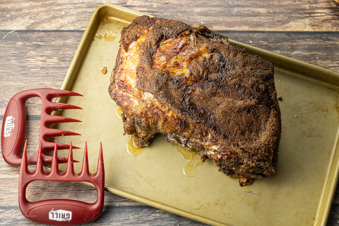 pork roast on a baking sheet with shredding claws