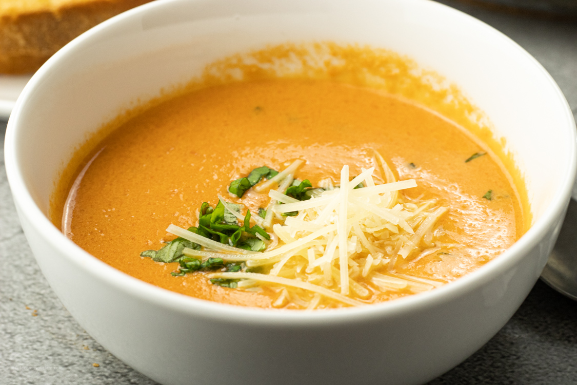 soup made from tomatoes topped with parmesan cheese and basil