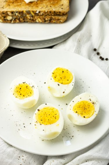 hard boiled eggs that have been cooked in an air fryer, sliced in half on a white plate