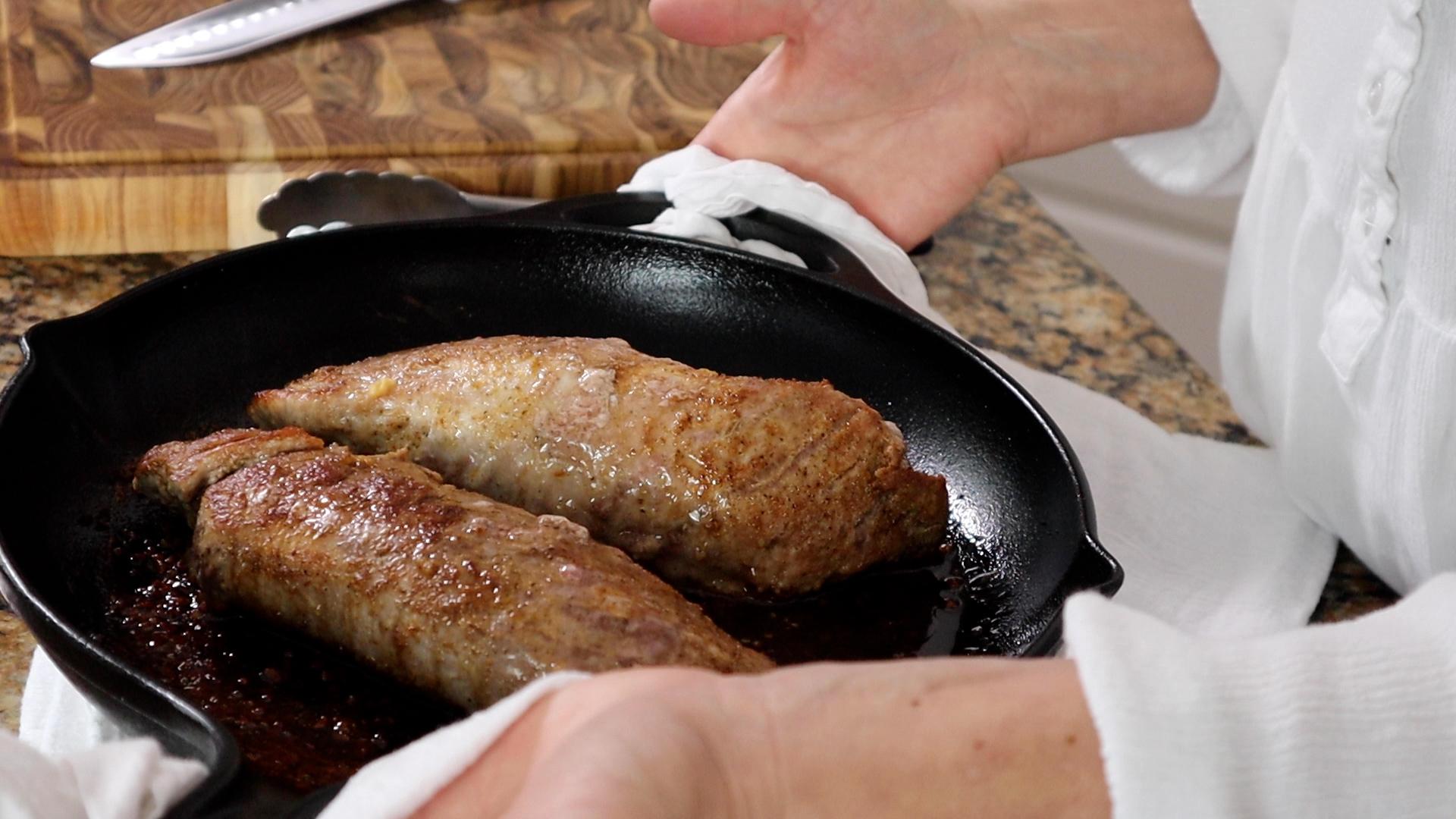 two pork tenderloins in a cast iron pan