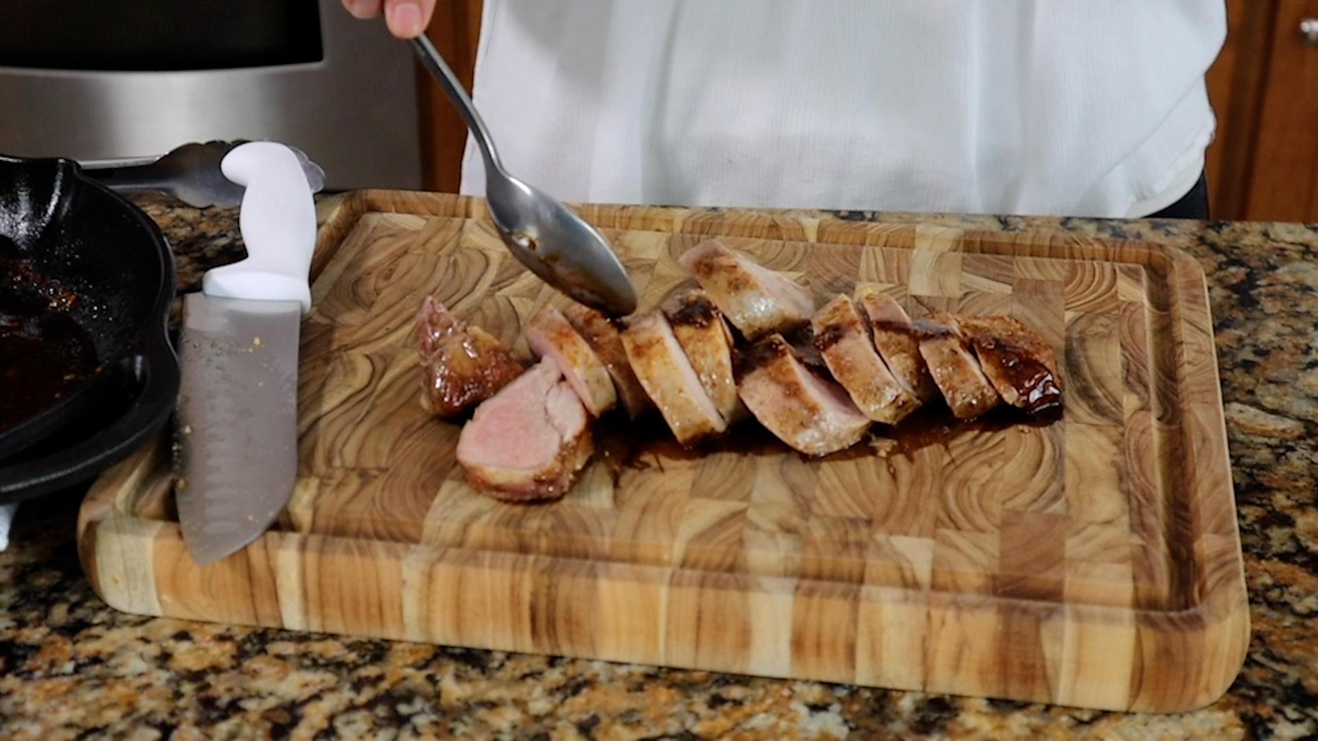drizzling balsamic glaze over sliced pork tenderloin