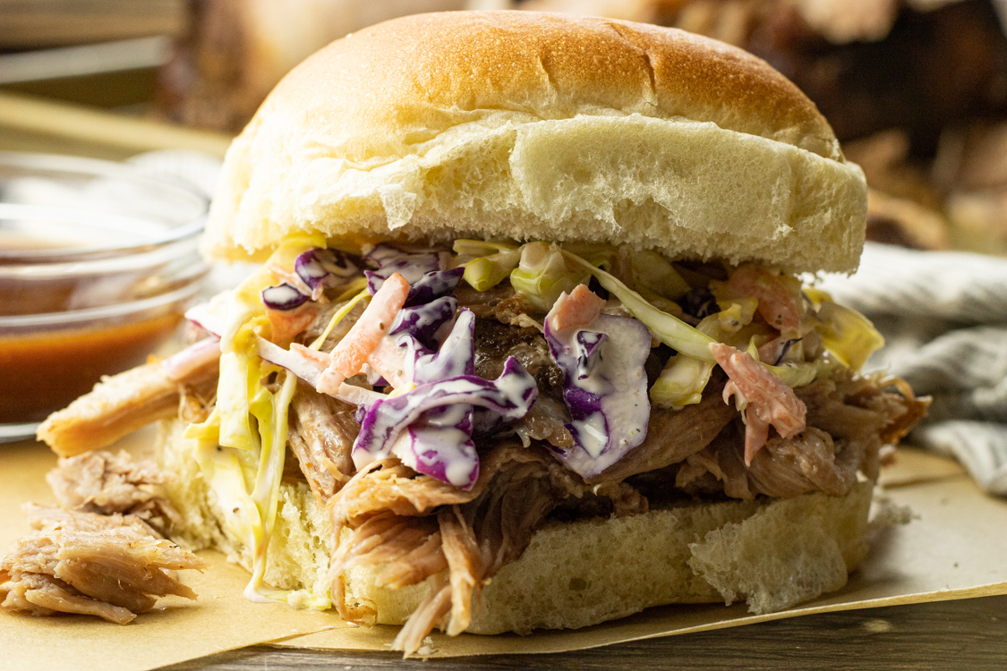 pulled pork sandwich topped with coleslaw salad
