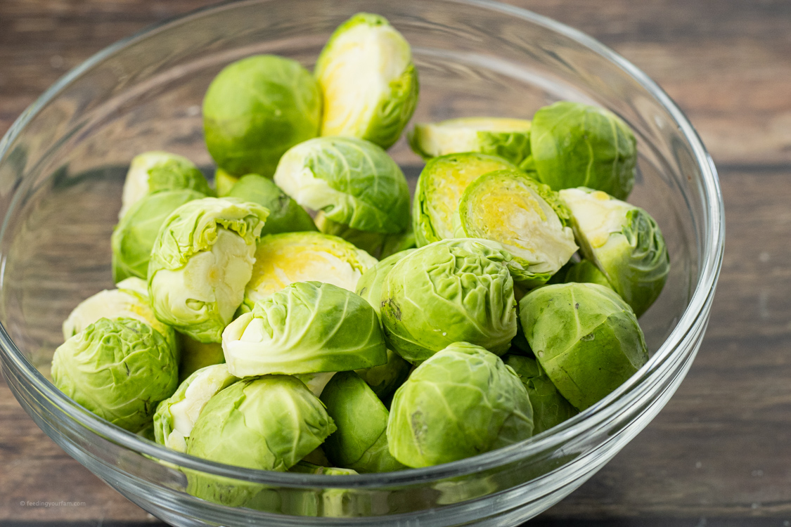 sliced, green brussel sprouts in a glass bowl