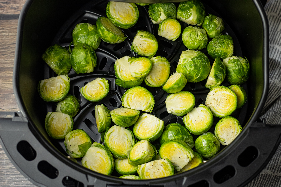 uncooked brussel sprouts in an air fryer basket