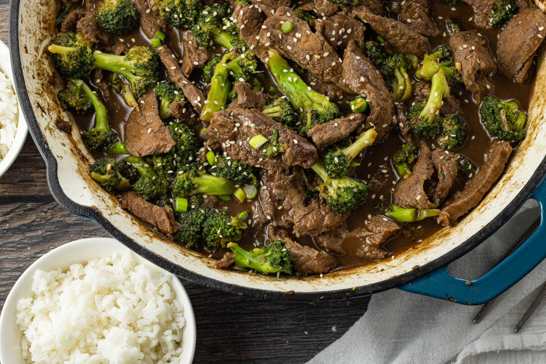 cooked broccoli beef in a pan next to a bowl of white rice
