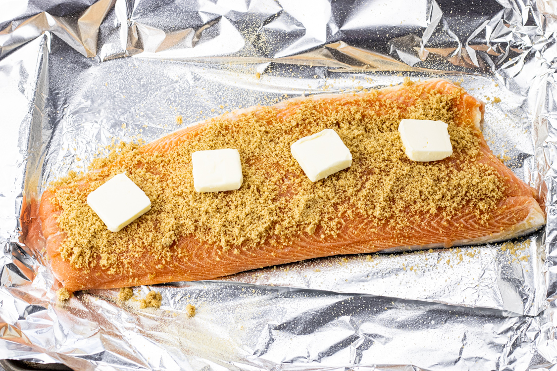 salmon filet on a piece of foil, topped with brown sugar and butter slices