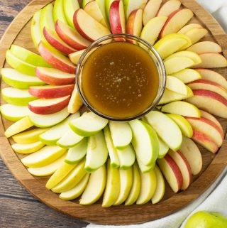 sliced apples surrounding dipping sauce made of caramel