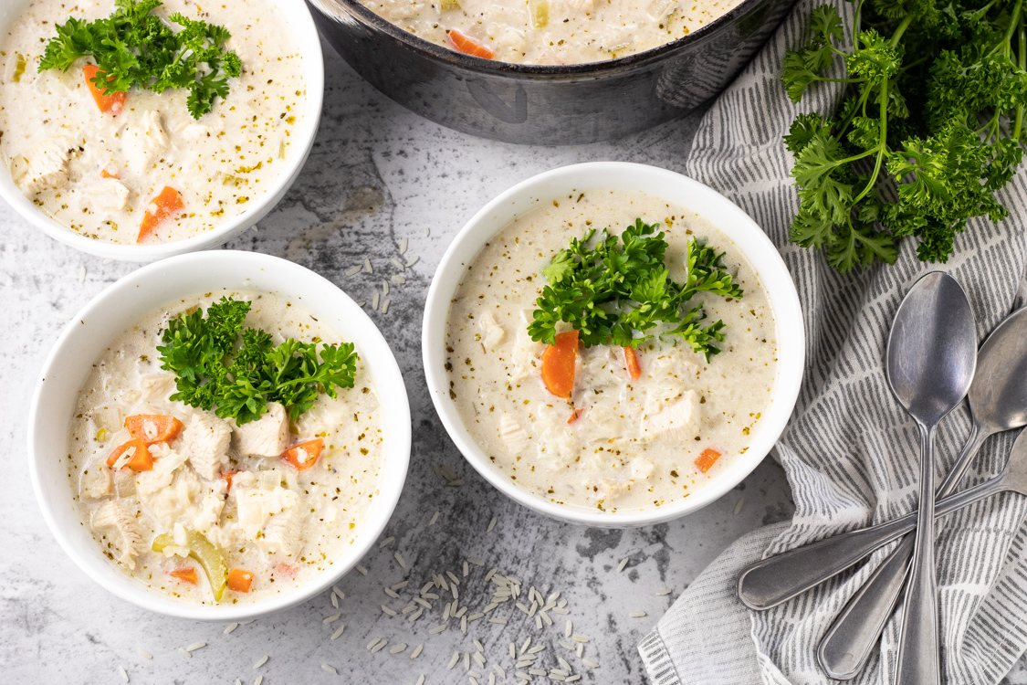 3 bowls of creamy chicken soup with rice topped with fresh parsley