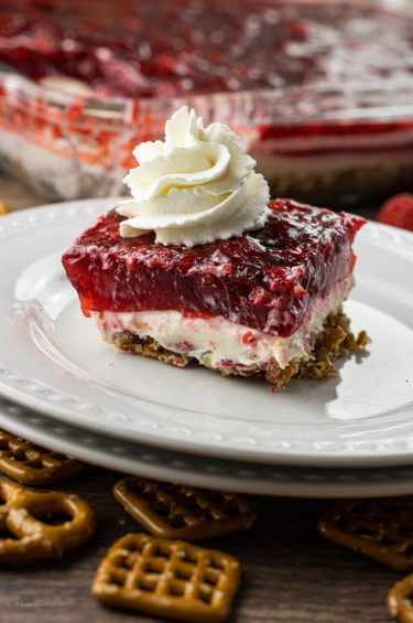 pretzel jello salad layered with pretzels on the bottom, cream cheese in the middle and raspberry jello on top