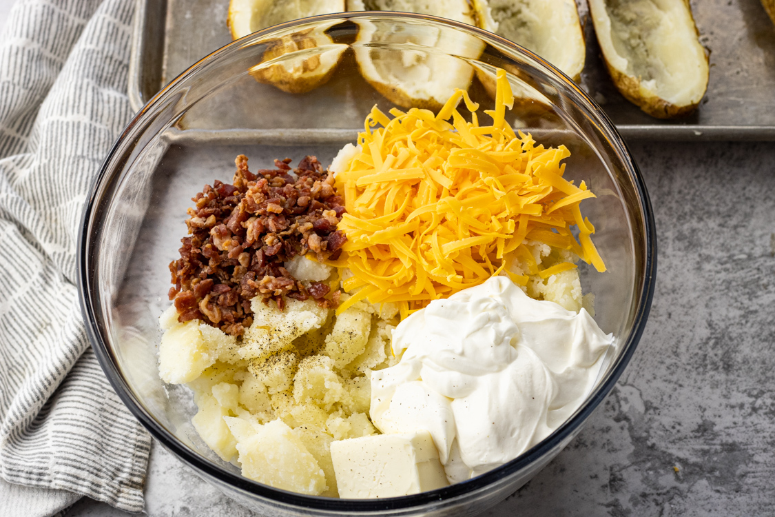 bowl with potatoes, cheese, butter, sour cream and bacon