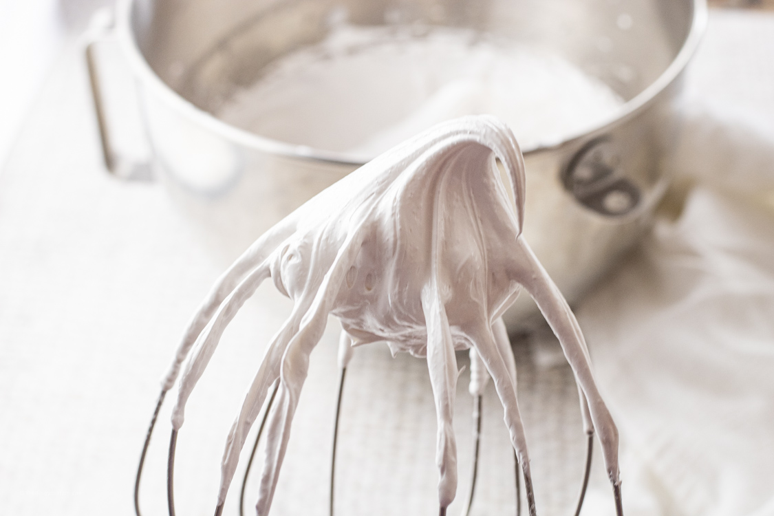stiff meringue egg whites on a whisk