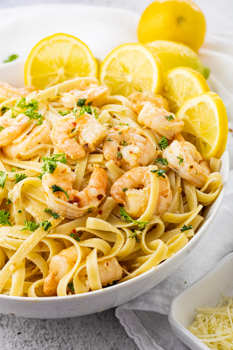 big white bowl of fettuccine noodles and shrimp with lemons