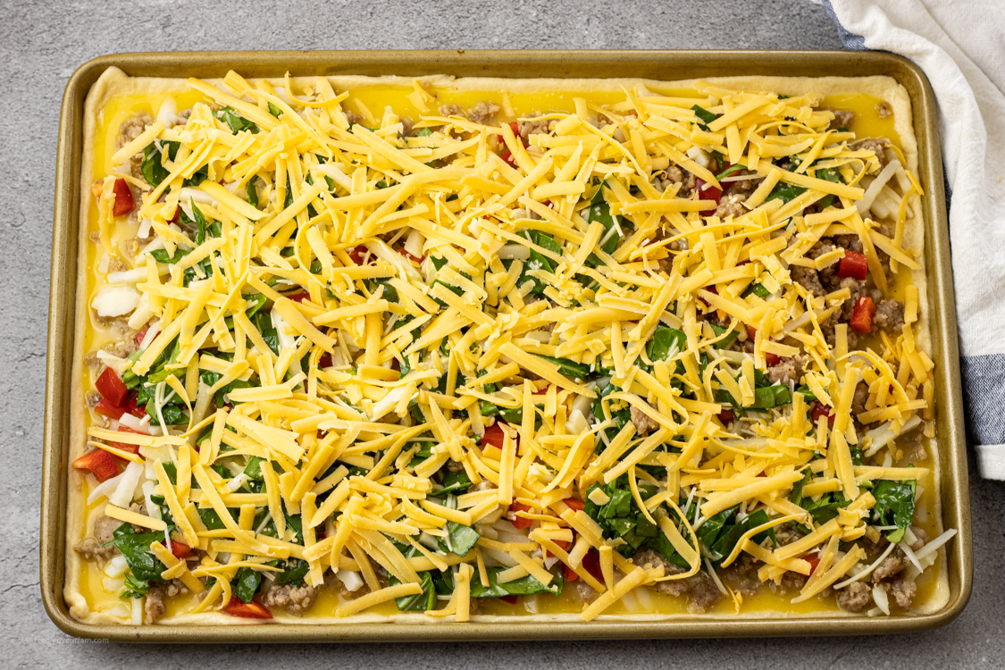 pizza for breakfast topped with sausage, eggs, hash browns and cheese ready to be baked