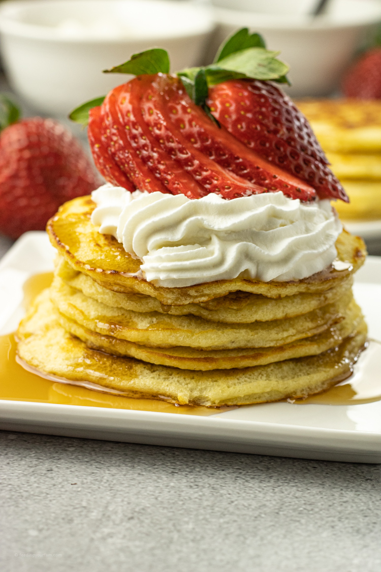 pile of pancakes topped with whipped cream and strawberries
