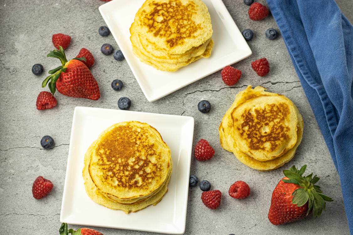 piles of cooked pancakes on white plates surrounded by berries