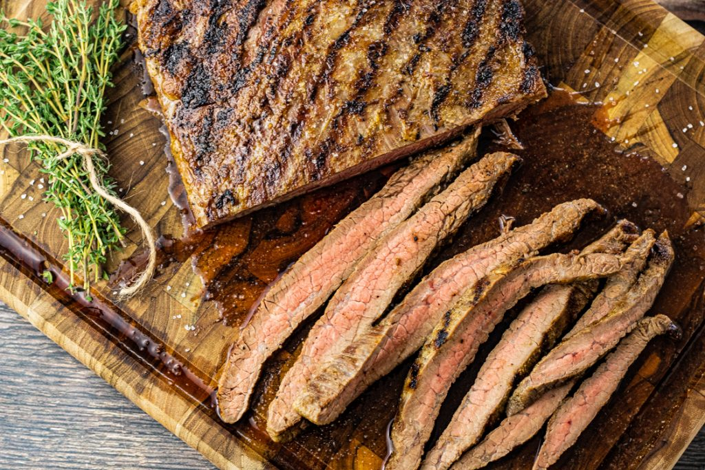 slice flank steak on a wooden cutting board
