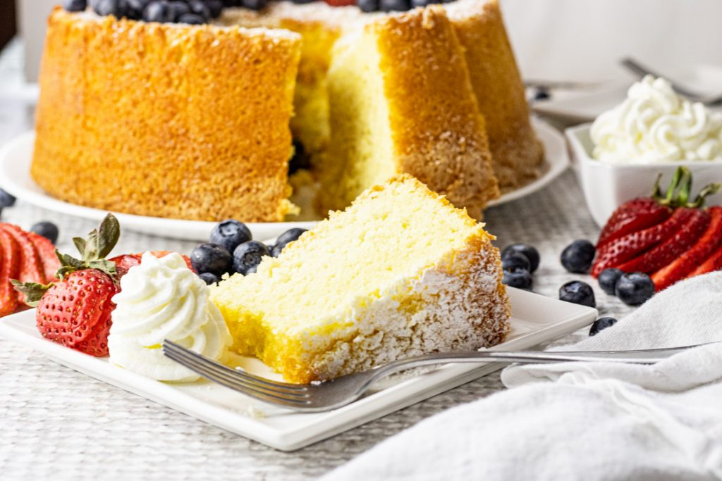 slice of chiffon cake on a white plate with whipped cream, strawberries and blueberries