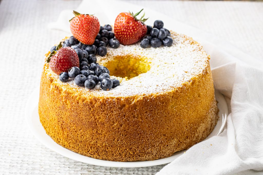 chiffon cake topped with powdered sugar, blueberries and strawberries