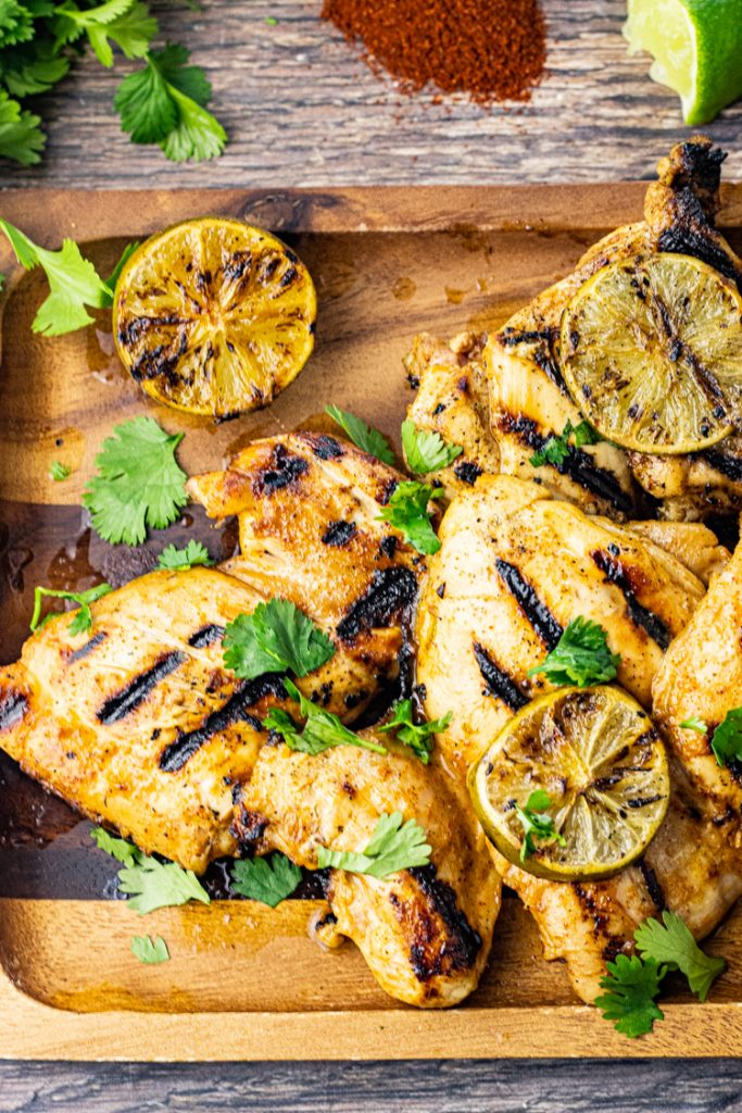 pieces of grilled chicken thighd on a wooden platter