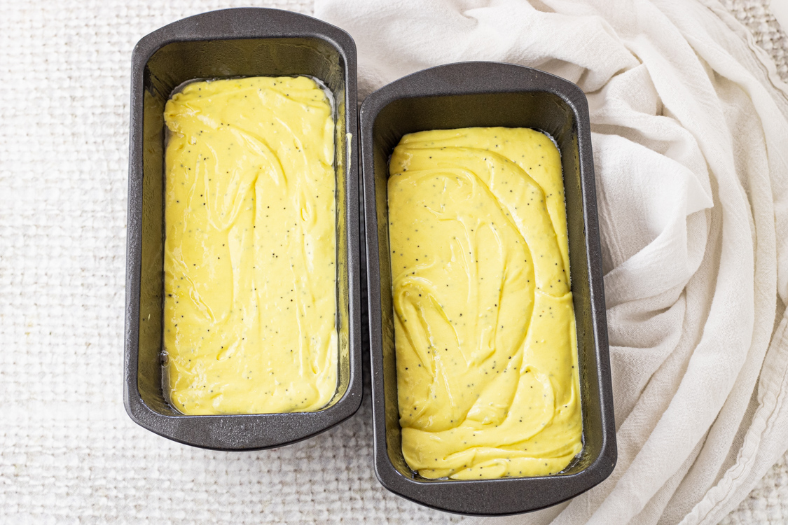 two loaf pans filled with yellow batter for lemon bread