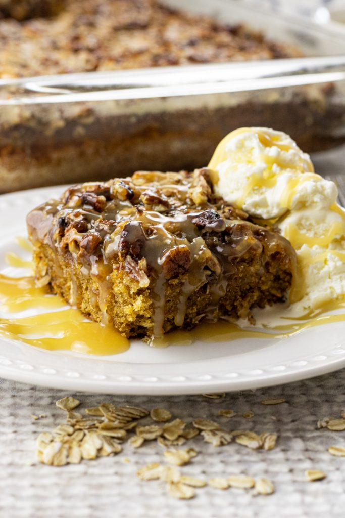 slice of oatmeal cake topped with coconut and pecans with vanilla ice