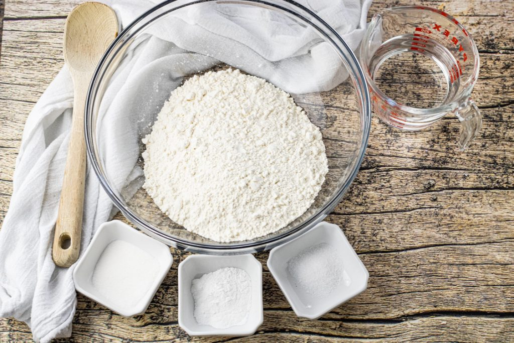 big glass bowl of flour surrounded by smaller bowls of sugar, salt and baking powder