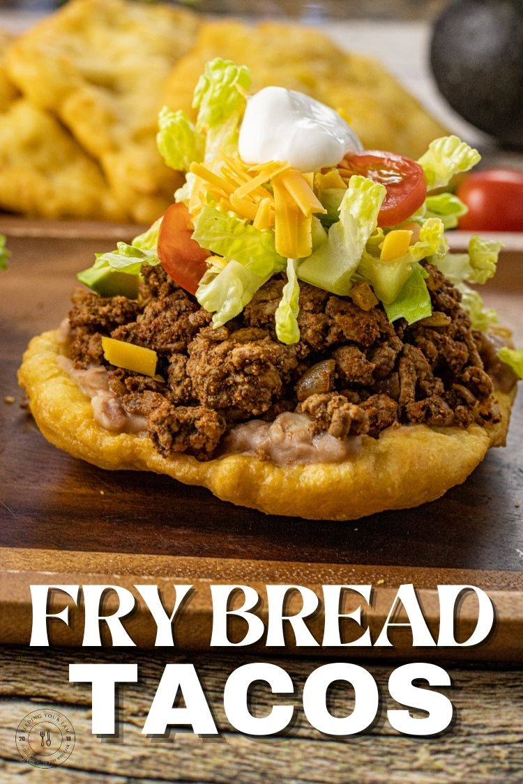 A simple Fry Bread made of a crispy outside and soft, chewy center is topped with refried beans, taco meat, lettuce, salsa, sour cream and all your favorite toppings to make this easy recipe for Fry Bread Tacos. This Fry Bread Taco Recipe will soon be on repeat on the family meal plan.