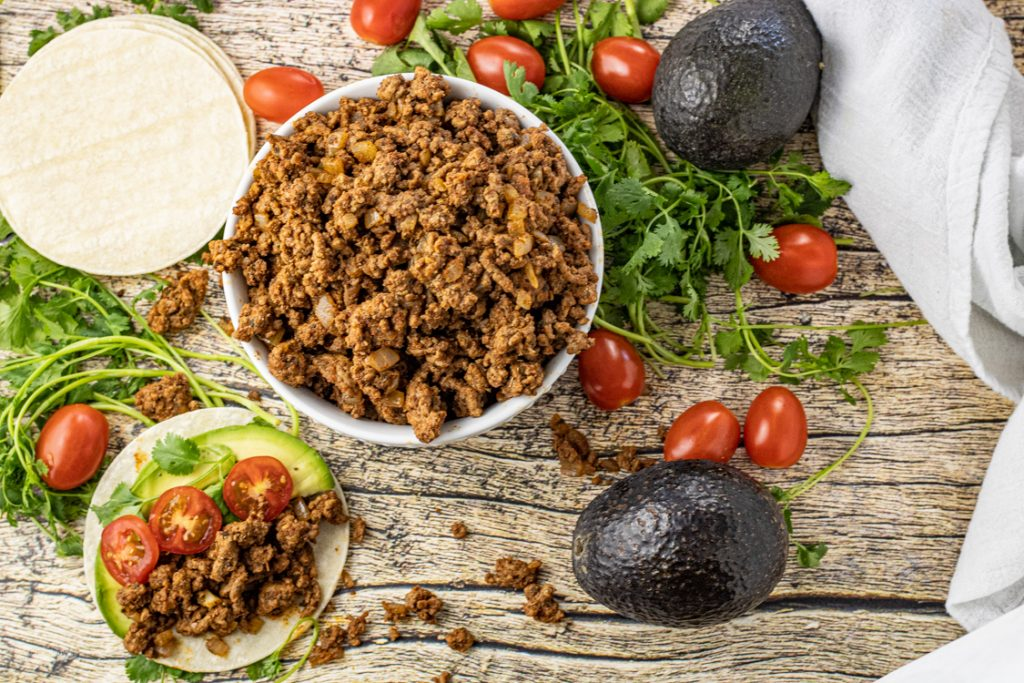 bowl of ground beef taco meat surrounded by avocados, cilantro and grape tomatoes
