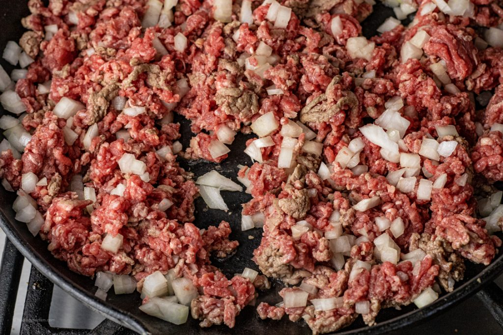 ground beef and diced onion in a cast iron pan