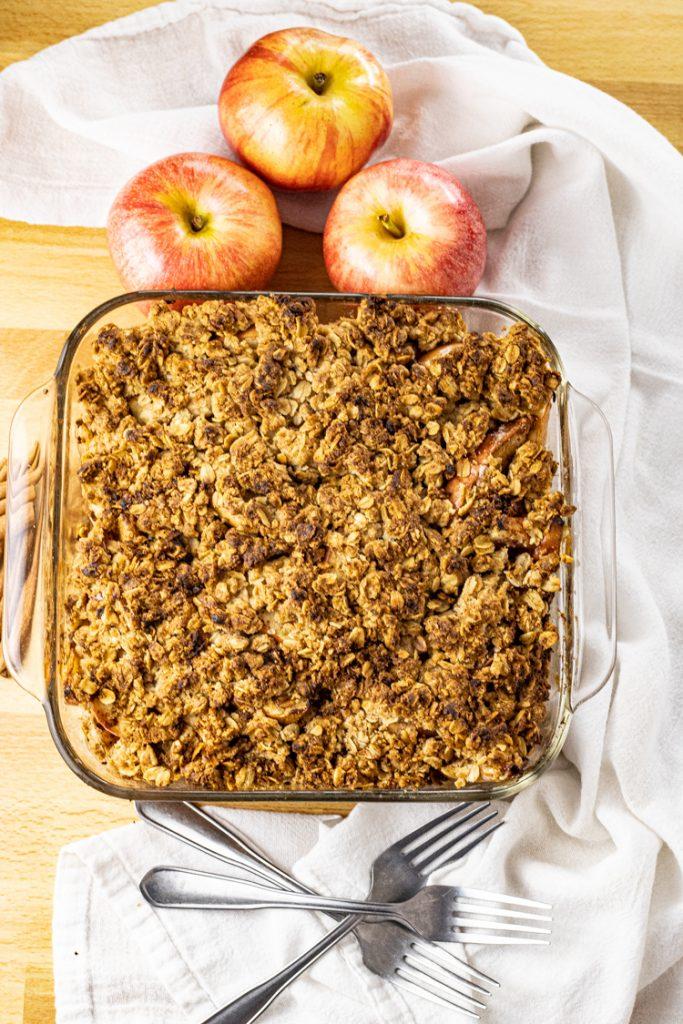 square pan of crunchy oat topping on apples for apple crisp