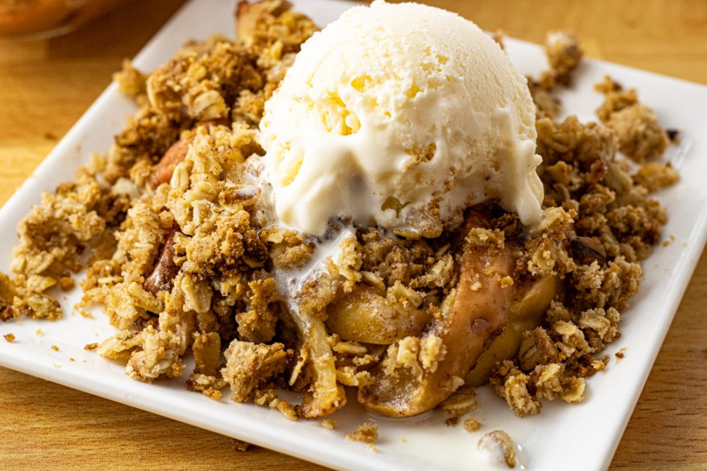 apple crisp on a white plate topped with vanilla ice cream