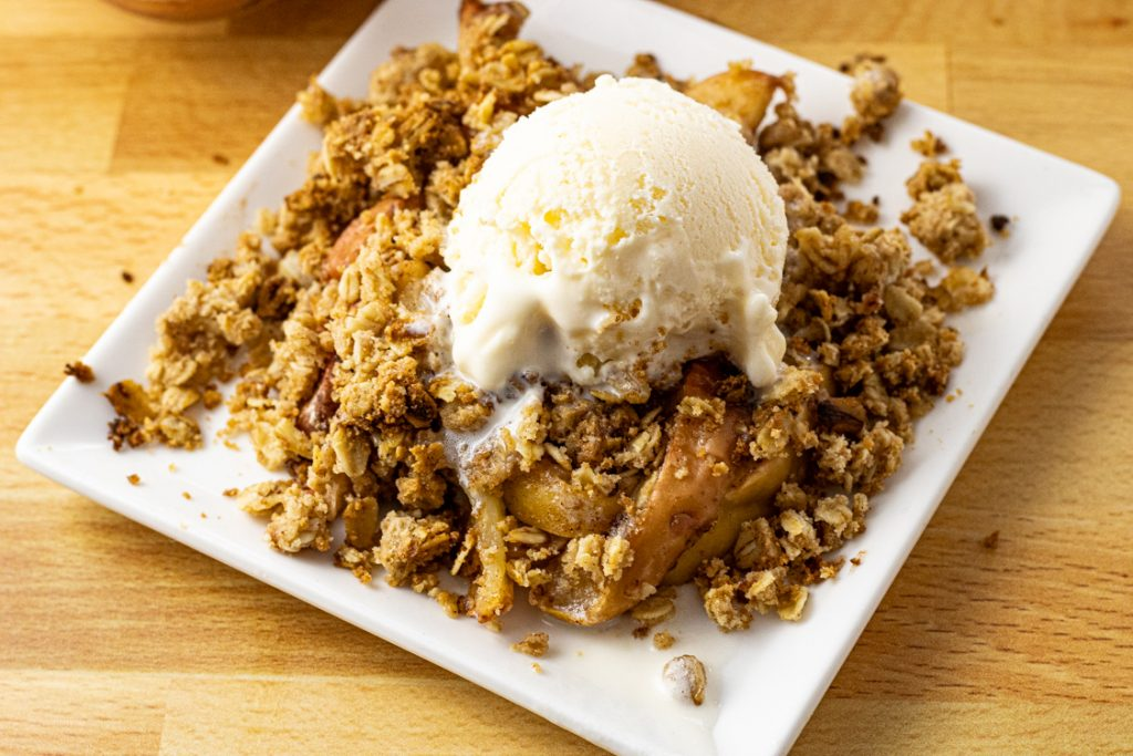 Baked apples with crisp oatmeal topping all topped with vanilla ice cream