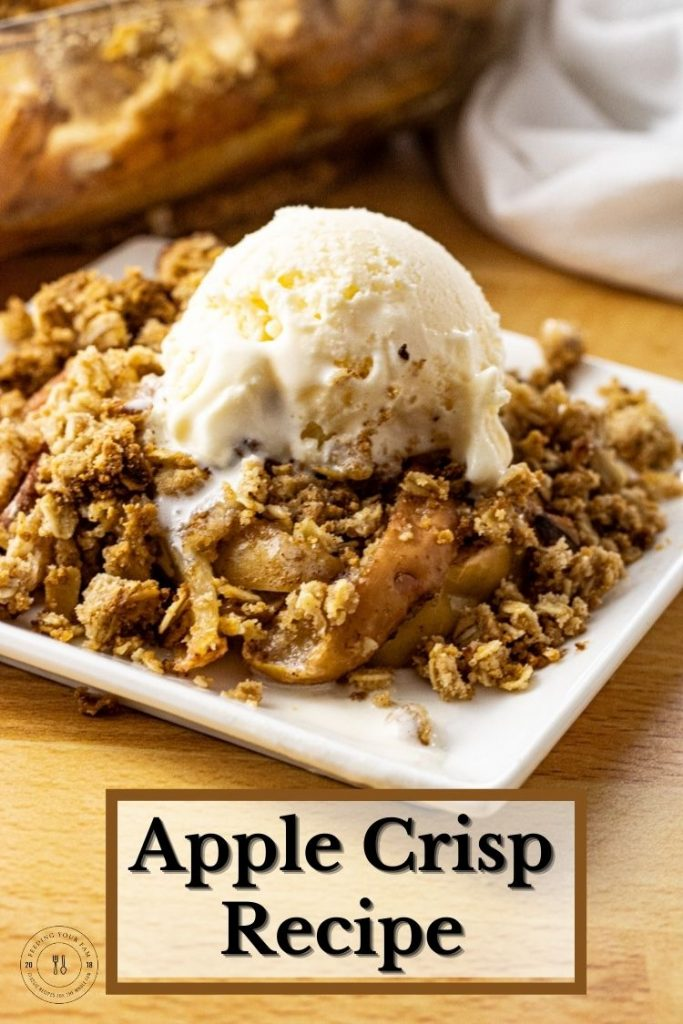 Apple crisp topped with vanilla ice cream on a white plate.