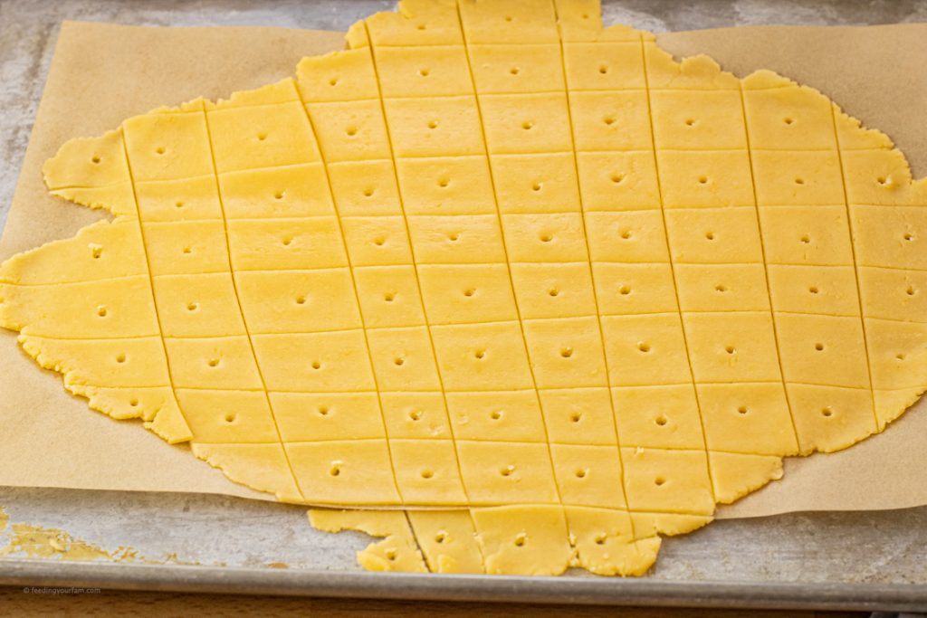 orange dough for crackers rolled out thin and sliced into squares with a small hole in the center