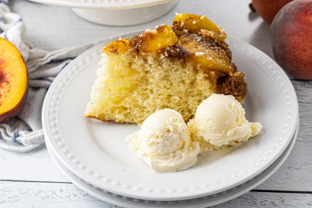 slice of peach upside down cake on a white plate with two scoops of vanilla ice cream