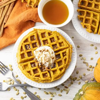 pumpkin waffles on a white plate topped with whipped cream