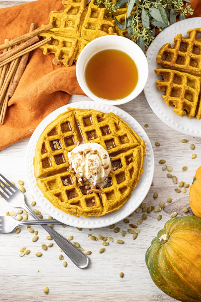 waffles made with pumpkin puree topped with whipped cream, cinnamon and maple syrup