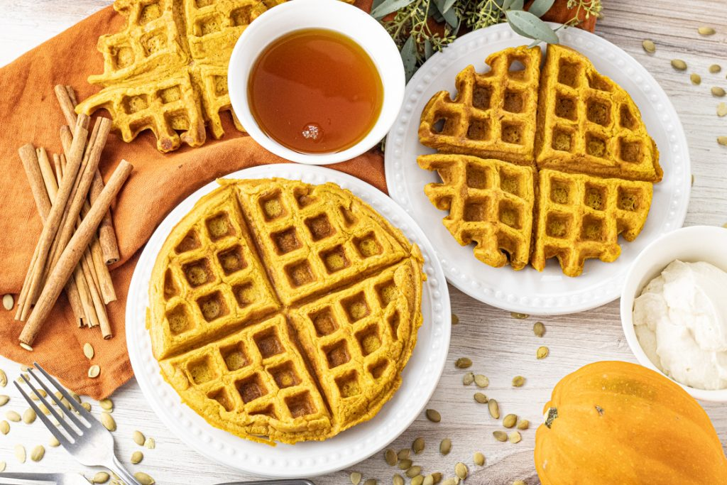 two white plates with orange colored pumpkin waffles on them.