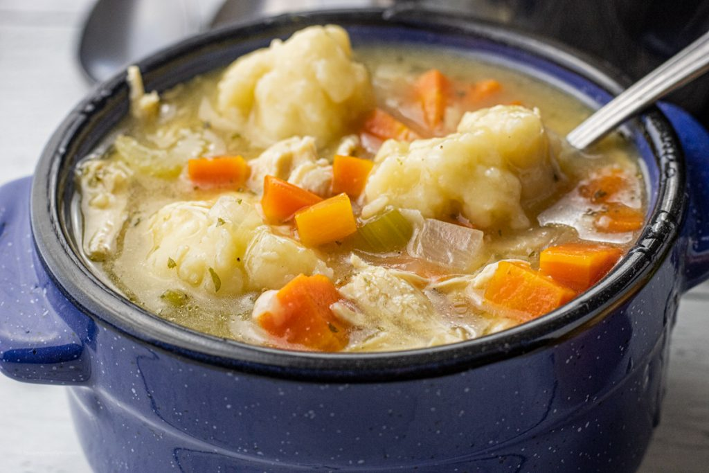 chicken and dumplings soup in a blue soup bowl